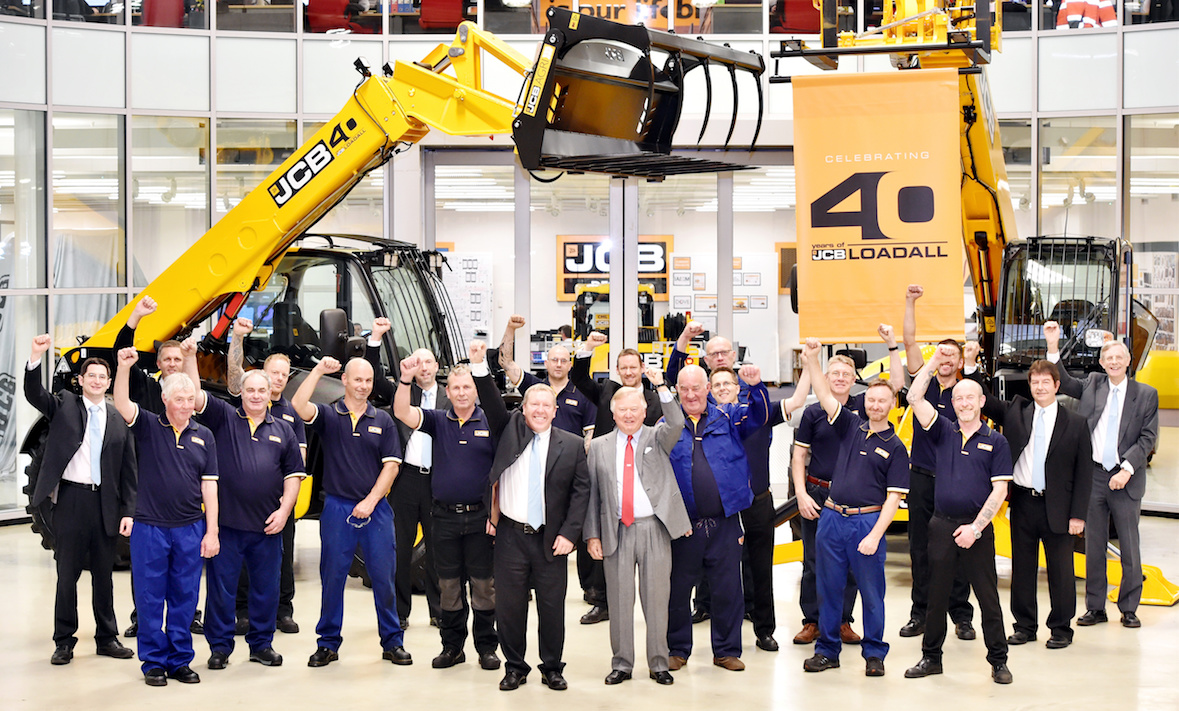 """Pictured is JCB Chairman Lord Bamford and Loadall MD Ian Pratt celebrating the 40th anniversary of the JCB Loadall with colleagues.  MANY HAPPY RETURNS AS LOADALL MARKS 40 YEARS IN PRODUCTION   JCB is today celebrating a major milestone in its long record of innovative machine design – the 40th anniversary of the Loadall telescopic handler.  First launched on October 20th 1977 the machine mechanised lifting and loading tasks on building sites more usually carried out by a small team of men. The potential for the Loadall in agriculture was also quickly harnessed and it went on to revolutionise materials handling tasks on farms, stacking bales, loading muck and shovelling grain, replacing rudimentary tractor mounted hydraulic loaders.  JCB has sold more than 220,000 Loadalls to date, generating more than £7 billion in sales - £4.5 billion of which has been from exports.  Daily output of JCB telehandlers at the World HQ in Staffordshire is currently at its highest level ever, with the number of machines built expected to increase by 25% by the end of the year compared to 2016. Such is the success of the product that one Loadall rolls off JCB's Rocester production line every six minutes. The business making the machines today employs more than 1,200 people.  Today JCB Chairman Lord Bamford said: """"When we launched the Loadall in 1977, we sold just 64 machines that year but we were very confident that the telescopic handler would grow in popularity simply because it made jobs so much easier on construction sites and on farms. """"The concept soon took off and the faith we put in the telescopic handler four decades ago has been repaid. It's wonderful to celebrate 40 years of success of the Loadall with production hitting historic levels. """"I'd like to congratulate everyone around the world who has contributed to this success over the past 40 years. We must now look forward to the next 40 years and build on what has been achieved so far."""" More . . . .   2/ . . . Eddie Finney, 5"""